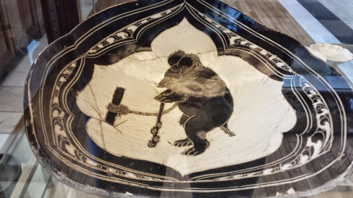 North Chinese (~11-12th century) ceramic plate depicting a funky, vaguely humanoid dancing bear tied to a pole.
